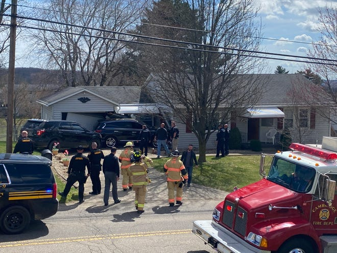 Emergency responders arrive at the scene where a high-speed pursuit that started on Interstate 77 came to a halt when the fleeing driver lost control of the vehicle and crashed into a home on Highland Avenue in Cambridge.