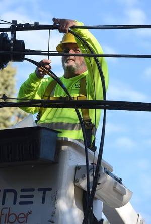 A worker installs fiber-optic cable outside a home.