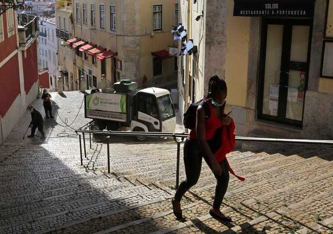 """FILE - In this Wednesday, June 24, 2020 file photo, a woman wearing a face mask walks past workers washing the street in Lisbon's old center. A senior European human rights official is sounding the alarm about a rise in racism and discrimination in Portugal. The Council of Europe's Commissioner for Human Rights, Dunja Mijatović, published a report Wednesday, March 24, 2021 into """"the increasing level of racism and the persistence of related discrimination"""" in the southern European country. (AP Photo/Armando Franca, File)"""