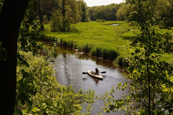 A kayaker floats down Pigeon River at Hemlock Crossing in West Olive, Mich. The Michigan Legislature has passed authorization projects for the Michigan Natural Resources Trust Fund.