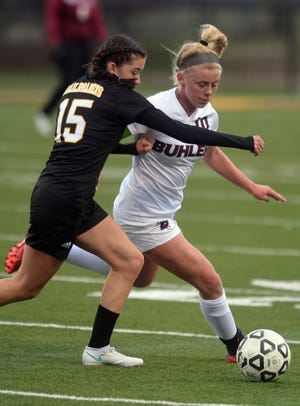 Buhler junior Aubrey Tanksley, right, is being challenged by Newton freshman Isabel Sandoval during the season opener at Fischer Field. Tanksley scored three goals with three assists in a 9-0 Buhler win.