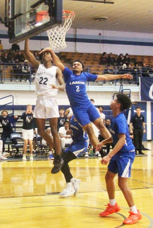 Otero Junior College's Ryan Stowers (22) drives to the basket against Lamar's Deondre Barfield in Monday's game at the McDivitt Center. Stowers scored 26 points in the Rattlers' 105-83 win.