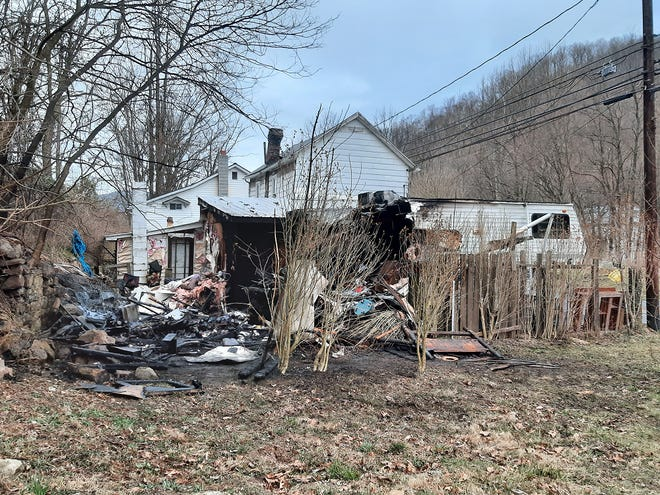 This Creekside Drive home was heavily damaged by fire Tuesday afternoon when a nearby storage shed and camper caught fire and the blaze spread to the rear of the home.