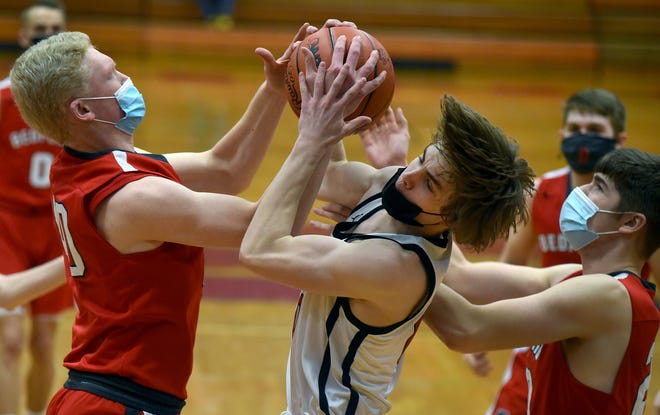Andrew McCarthy of Monroe tangled up Andrew Hollinger of Bedford with John Jensen in on the play in the first round of the D1 Districts at Monroe High School Tuesday, March 23, 2021.