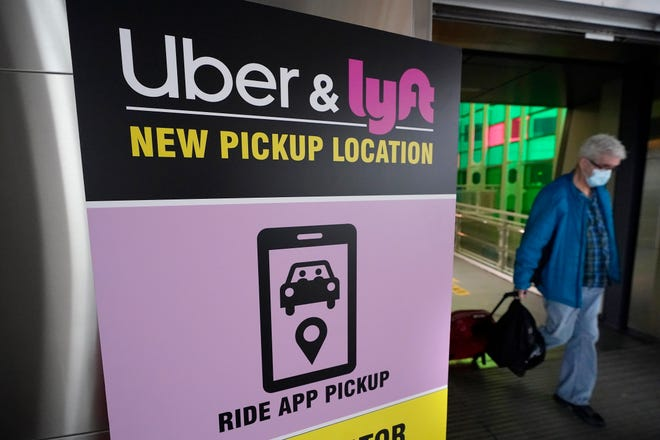 A passer-by pulls luggage while walking past a sign offering directions to an Uber and Lyft ride pickup location at Logan International Airport in Boston on Feb. 9, 2021. Businesses like Uber, Airbnb and Square were born in recessions. Now, the effects of COVID-19 are forcing existing businesses to reinvent themselves, and some of today's most significant business obstacles will spark new startups offering innovative solutions. [AP Photo/Steven Senne]