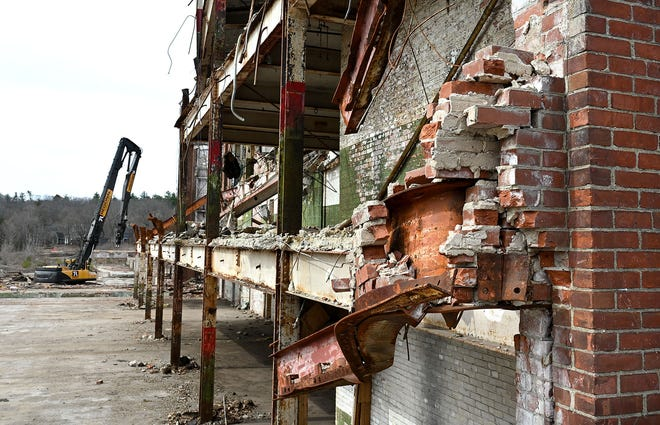 Broken bricks are shown on a corner of the Draper Mill factory facing Hopedale Street as demolition continues, March 24, 2021.