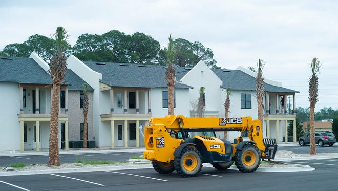 A lift sits next to new residential construction on County Road 393 in South Walton County. Development and real estate transactions are booming in South Walton even as county officials take steps to curtail some of that development.