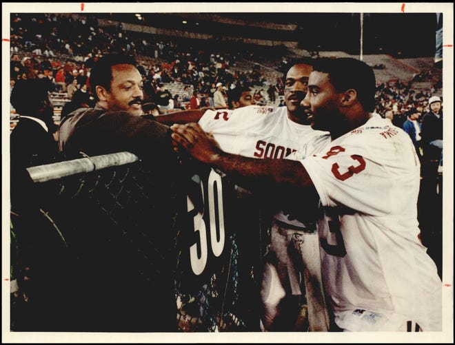 Sooners Kenyon Rasheed (33) and Mike Gaddis meet the Rev. Jessie Jackson at the 1991 Gator Bowl.