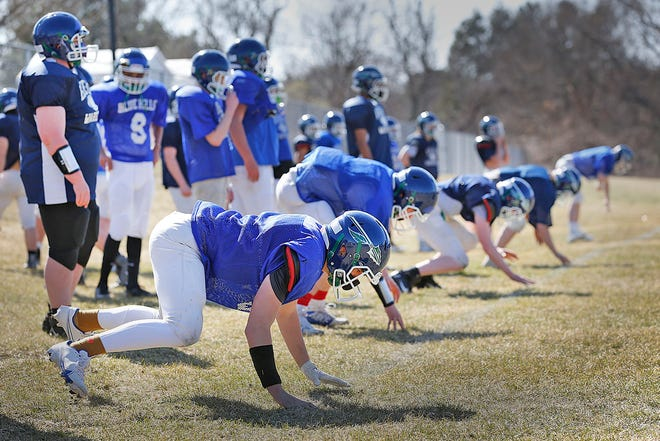 Players practice getting off the line on a snap count.Blue Hills VoTech Warriors football team members practice for the first game of the season on Wednesday March 24, 2021 Greg Derr/The Patriot Ledger