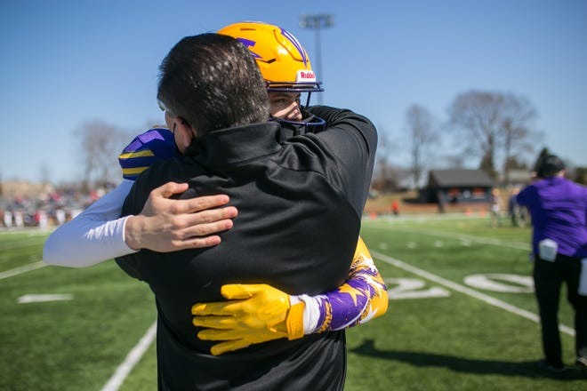 Kurt Whisenand hugs his son Hononegah's Isaac Whisenand after a good play against Belvidere North in the second quarter of their game at Harlem High School on Saturday in Machesney Park. Hononegah beat Belvidere North, 61-0.