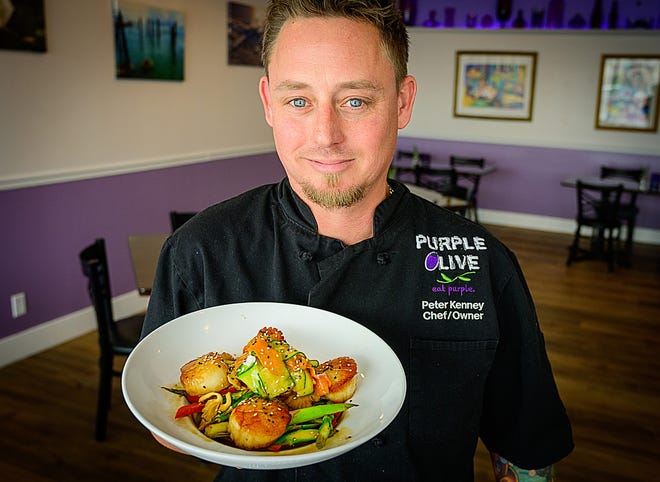 Peter Kenney, owner and chef of Purple Olive, holds a plate of lemon tamari scallops in the dining room of his restaurant in St. Augustine Beach on Monday.
