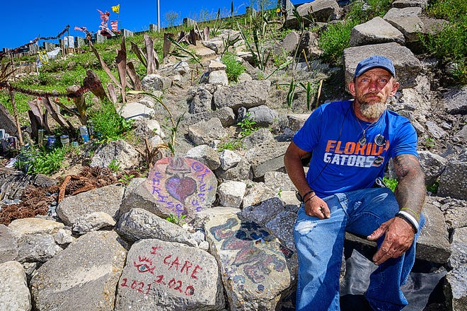 """Brian Freeman sits in an area on the west side of the bridge on U.S. 1 that crosses Moultrie Creek, where he has built what he calls the """"sanctuary."""" He has decorated the spot with items found on the road, flowers and messages of love and peace. The area has since been cleared by the Department of Transportation."""