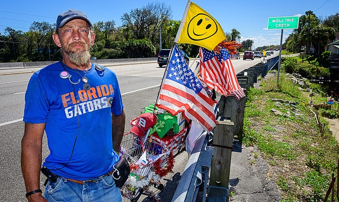 Brian Freeman stands by his bike on the side on U.S. 1, south of St. Augustine, last week. Freeman, who is homeless, spends his days collecting trash from the side of the road as his way to serve God and help the environment.