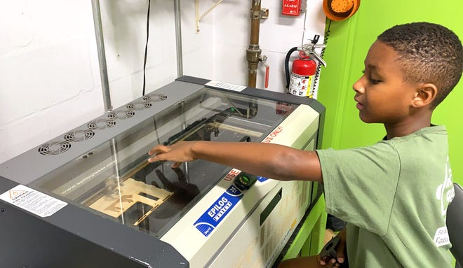 Zaylon, a Suncoast Science Center/Faulhaber Fab Lab engineering camper, uses the lab's laser cutter to customize a project.