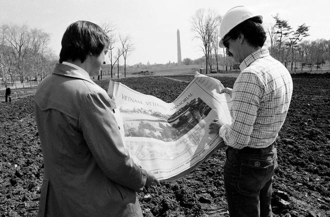 Jan Scruggs, left, president of the Vietnam Veterans Memorial Fund and Gary Wright, the project engineer for the memorial, look over plans for the project in Washington on March 23, 1982. The memorial was built on this site near the Washington Monument. Groundbreaking was on March 26, 1982.