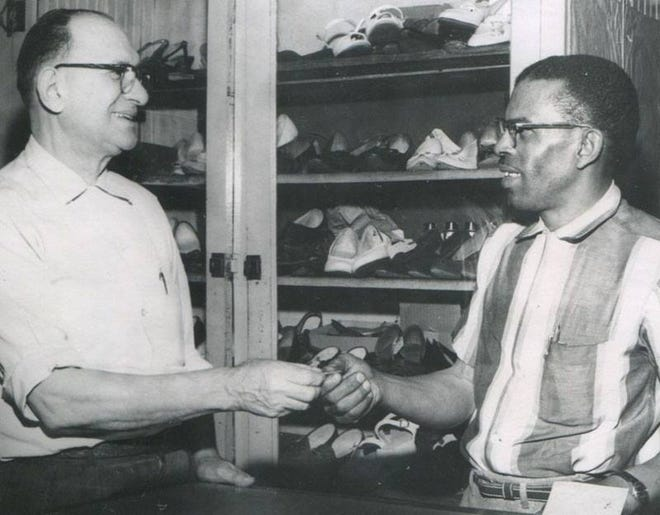 Greek immigrant Dave Vlahos, left, hands the key to his shoe shop to new owner John Easley on May 25, 1961. Easley, who started shining shoes in the shop when he was nine years old, owned the business until 1972.