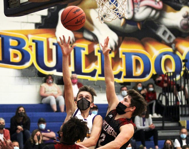 Bronson's Aden Hathaway scores two points in overtime against White Pigeon in district play on Tuesday.