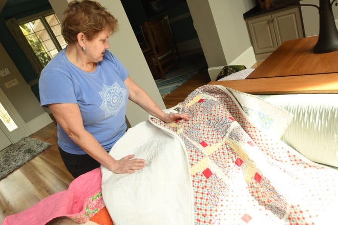 Melanie Kelley looks over one of the quilts that was found in Ash, N.C., after a tornado destroyed Phyllis O'Connor's house in Ocean Ridge Plantation. Kelley, who is now collecting the quilts and others for Rose House in honor of Phyllis O'Connor, said they have more than tripled the number of quilts they had collected thanks to the community.