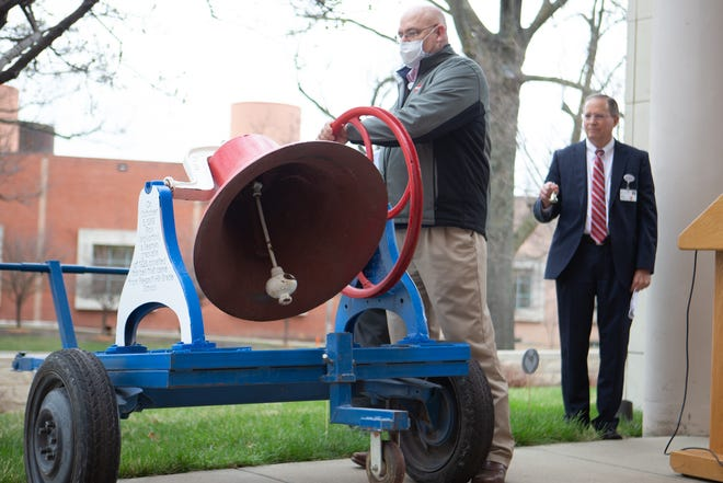 Keith Griffin, manager of design and construction at Stormont Vail Health, rings the Pleasent Hill Grade School bell as Robert Kenagy, CEO and present of Stormont Vail, joins community members Wednesday in a memorial to the lives lost to COVID-19.
