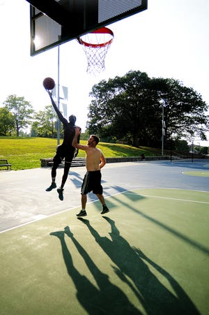 Two men play a friendly game of one-on-one at the University Park basketball court on Aug. 11, 2016.