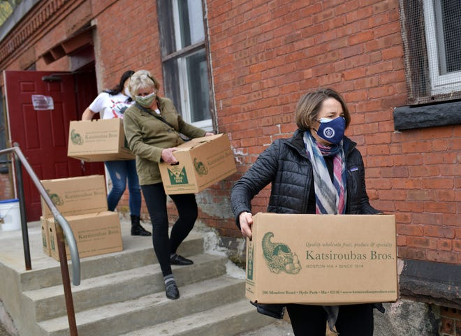 Attorney General Maura Healey carries a box of food to a car with Rep. Mary Keefe following. Keefe, Rev. Jose R. Perez, Congressman Jim McGovern and Healey met at the food pantry attached to the Rock of Salvation Pentecostal Church, Food Distribution Center, 829 Main St., Worcester, Wednesday,