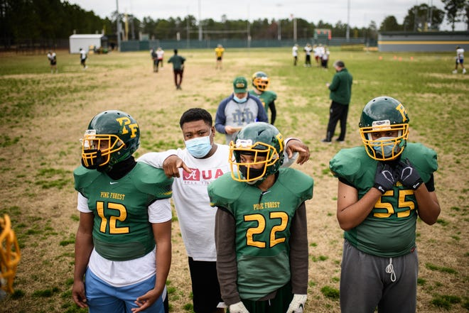 Coach Rob Jones talks with the Pine Forest defensive line players at football practice on Monday. [Andrew Craft/The Fayetteville Observer]