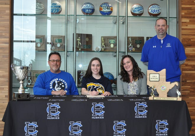 Signing a Letter of Intent is Tory Thompsonseated between her father Tod and her mother Marcy, along with Harrison Central Athletic Director Ray Hibbs.