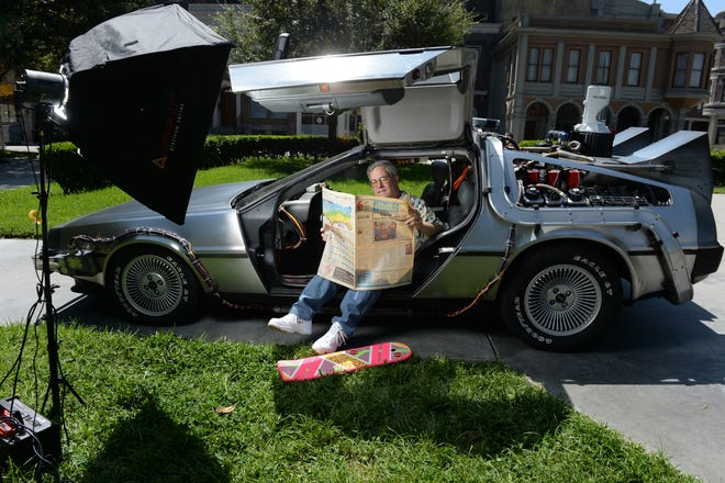 "Bob Gale, co-writer and co-producer of the ""Back to the Future movies,"" looks over a copy of USA TODAY while sitting in a restored DeLorean time machine owned by screenwriter Terry Matalas in Courthouse Square at Universal Studios, Los Angeles, in 2015."