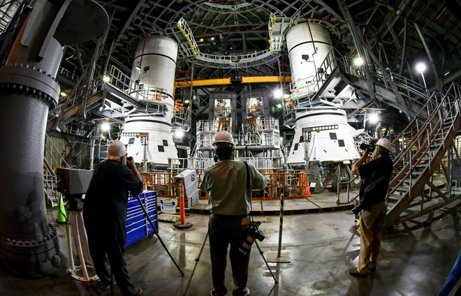 Members of the news media get a glimpse at the newly stacked booster rockets for NASA's Artemis I mission inside the Vehicle Assembly Building at Kennedy Space Center. The twin five-segment boosters will provide more then 75% of the thrust for SLS during launch. Craig Bailey/FLORIDA TODAY via USA TODAY NETWORK