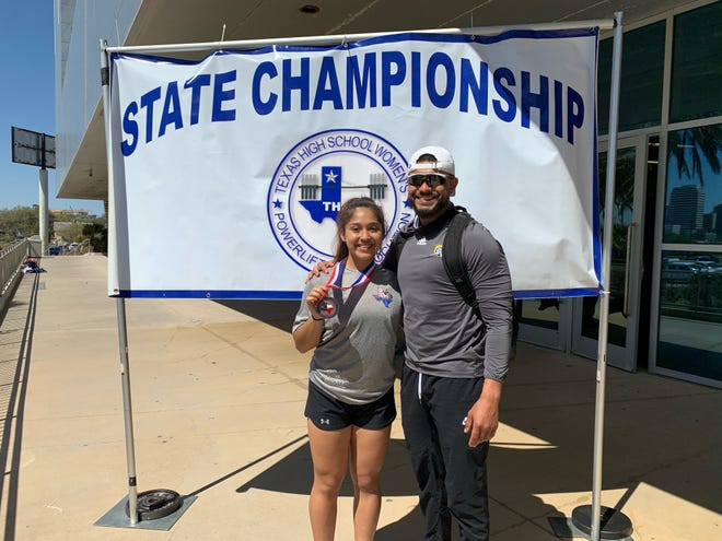 John Paul II's Samantha Sullivan takes a photo with athletic director Andrew Leon after the Texas High School Women's state powerlifting meet at the American Bank Center.