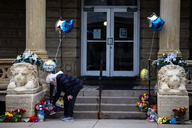 A man places a small statue outside of the main entrance to the Anamosa State Prison, on Wednesday, March 24, 2021, a day after a nurse and correctional officer were killed while on duty, in Anamosa, Iowa.