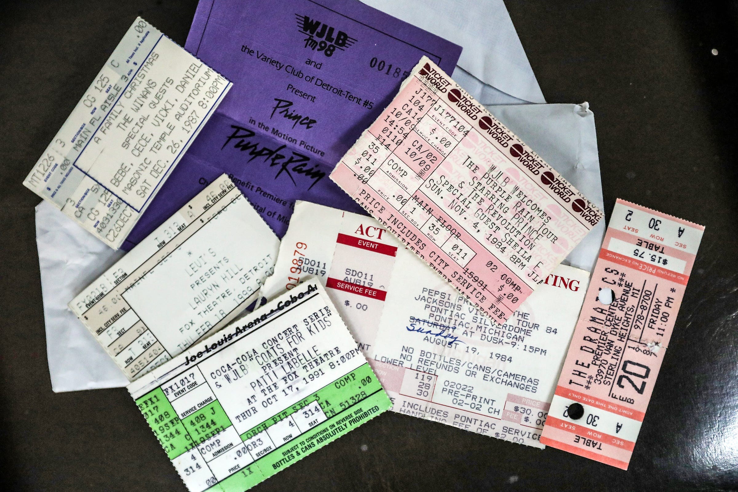 """Lee Robinson looks over old concert ticket stubs, like the ticket to see Prince and the Revolution with special guest Sheila E that opened his tour at Joe Louis Arena in Detroit on Nov. 4, 1984. Robinson, who worked for WJLB radio station at the time, gets his hair cut by Barber Hobson """"Hoppy"""" Colvin, where he often talks about music at Big D's Barber and Unisex Salon in Detroit, photographed on Wednesday, March 11, 2020."""
