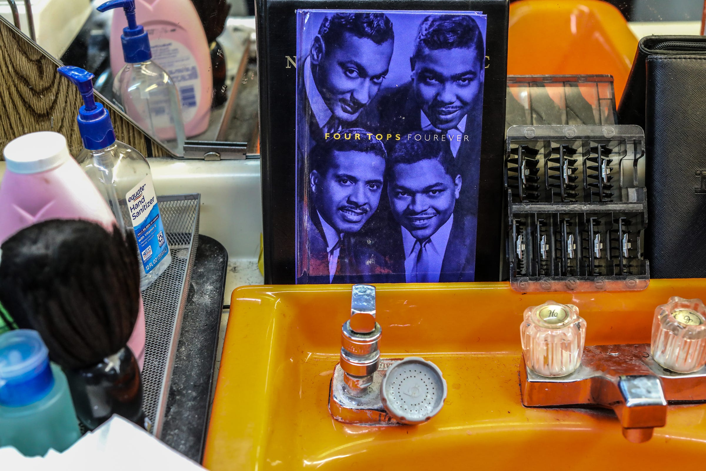 A book about the Motown group The Four Tops was given to Hobson ÒHoppyÓ Colvin, who has cut hair in Detroit for 58 years, including many clients that obtained stardom through music like the Four Tops at Big D's Barber and Unisex Salon in Detroit, photographed on Wednesday, March 11, 2020.
