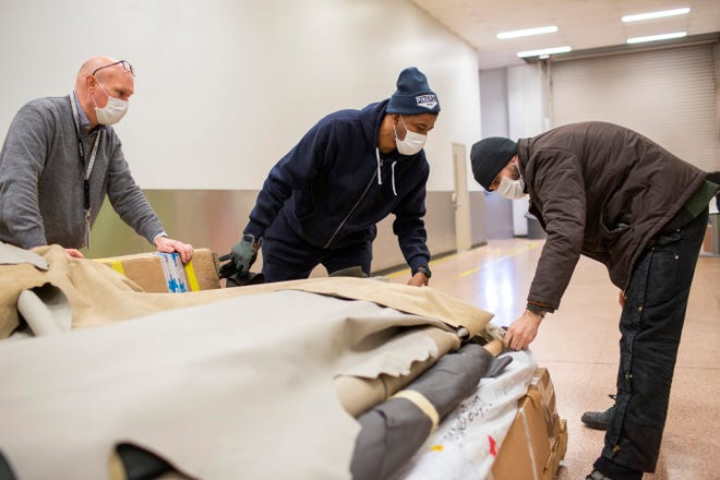 Left to right: Jim Conner, Ford 3D process director, is helping Nathaniel Crawford III and Jarret Schlaff, co-owners of Pingree Detroit, prepare to transport thousands of dollars in donated leather hides.