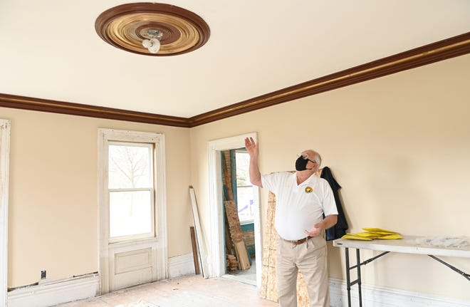 John Owsinex, 79, dari Walled Lake City Council, menunjuk ke medali langit-langit asli tahun 1850 di ruang tamu rumah.