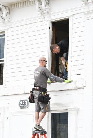 Mike Kuehnle, 40, kiri, penginstal windows Khusus Windows & Remodeling, dan kepala krunya, Alex Stonepainter, 47, bersiap untuk memasang jendela di Rumah Pertanian Banks-Dolbeer-Bradley-Foster di Taman Riley di Walled Lake.