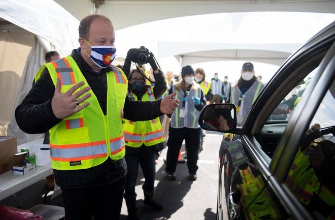 Colorado Gov. Jared Polis speaks with a motorist waiting for her shot on the opening day of the mass vaccination site at The Ranch events complex in Loveland, Colo. on Wednesday, March 24, 2021.