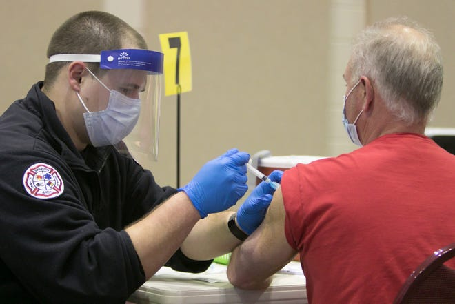 Brighton Area Fire paramedic Jason Wisby administers the COVID-19 vaccine to Pinckney resident Dwight Barclay Wednesday, March 24, 2021 at Chilson Hills Church. Arranged by the Livingston County Health Department, vaccinations are given by appointment only.