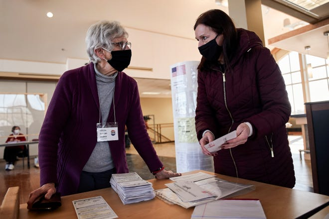 Diane Coenen, Oconomowoc city clerk, drops off absentee ballots to polling station Chief Inspector Arlene Ziety, as she makes her rounds during a primary election on Feb. 16.  Coenen is set to oversee another election during the COVID-19 pandemic.