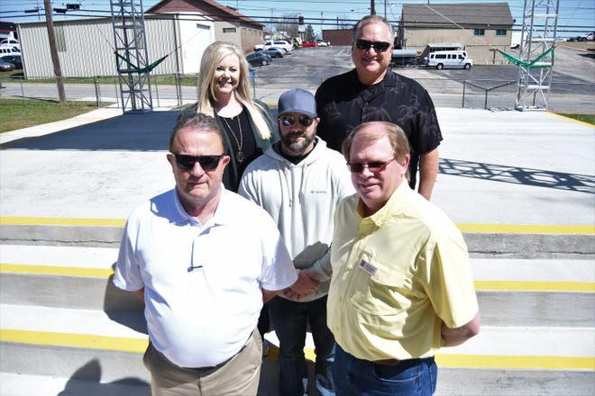 The Baxter Healthcare Summer Concert Series will return for its second year at the end of May. Gathering in Hickory Park on Wednesday for this photo was (front row, from left) Mountain Home Mayor Hillrey Adams; Ricky Johnson, GM/owner of Quality Inn and Suites and a member of the Mountain Home Advertising and Promotion Committee;  (middle row) Rickey Crawford, Summer Music Series coordinator; (back row) Amber Henry, marketing and community relations administrator for Farmers and Merchants Bank; and Mark Meyer, plant manager for Baxter Healthcare.