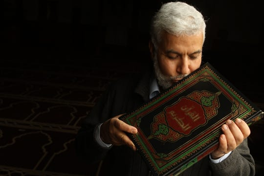 Ahmed Shedeed, president of The Islamic Center of Jersey City, New Jersey, kisses the  Quran, at the Islamic Center of Jersey City, on Wednesday, March 24, 2021.
