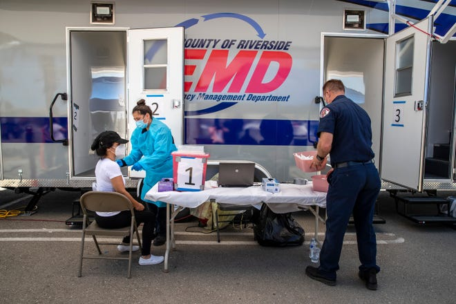 Emergency Medical Technician Sharon Lopez administers the Pfizer COViD-19 vaccine to Maria Cervantes during a Riverside County mobile vaccine clinic in Mecca Calif., on March 24, 2021.