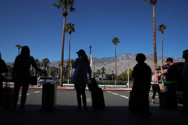 Travelers exit the Palm Springs International Airport in Palm Springs, Calif., on March 24, 2021.
