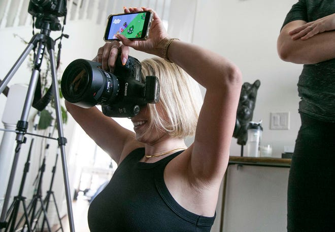 Photographer Luela Kaba photographs her clients in her home studio while playing Peppa Pig so her clients' daughter looks at the camera at Kaba's home in Phoenix on March 24, 2021.