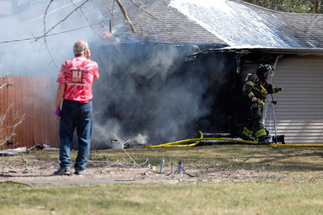 Firefighters work to extinguish a house fire on Griswold Road Wednesday afternoon.