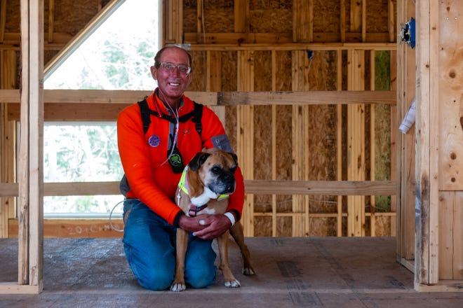 Randy Reidel poses for a portrait in his partially constructed house with his 13-year-old dog Courage on Wednesday, March 24, 2021, in Clyde Township. Reidel, who was diagnosed with terminal lung cancer, bought the property about 10 years ago and is determined to finish the house.