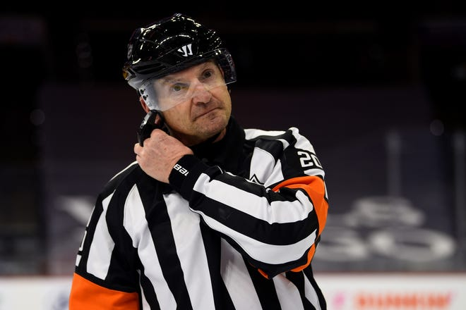 """FILE - Referee Tim Peel is shown during an NHL hockey game between the Philadelphia Flyers and the New York Islanders in Philadelphia, in this Saturday, Jan. 30, 2021, file photo. Tim Peel's career as an NHL referee is over after his voice was picked up by a TV microphone saying he wanted to call a penalty against the Nashville Predators. The league on Wednesday, March 24, 2021, announced that Peel """"no longer will be working NHL games now or in the future."""" The 54-year-old Peel had already made plans to retire next month.(AP Photo/Derik Hamilton, File)"""