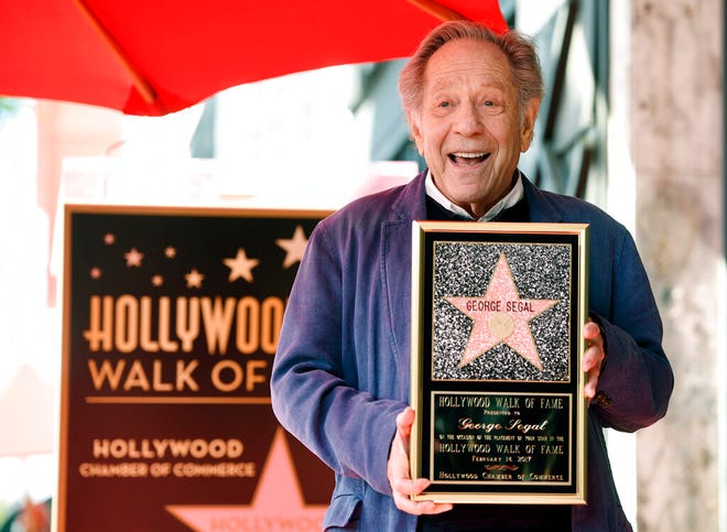 """FILE - Actor George Segal poses with a replica of his star at a ceremony honoring him on the Hollywood Walk of Fame in Los Angeles on Feb. 14, 2017. Segal, the banjo player turned actor who was nominated for an Oscar for 1966's """"Who's Afraid of Virginia Woolf?,"""" and starred in the ABC sitcom """"The Goldbergs,"""" died Tuesday, his wife said. He was 87.  (Photo by Chris Pizzello/Invision/AP, File)"""