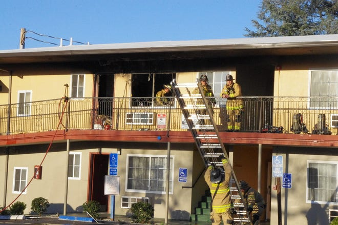 Firefighters work on a fire at the Sundial Lodge at 1055 Market St. in downtown Redding on Tuesday, March 23, 2021. One woman was taken to the hospital with serious injuries.