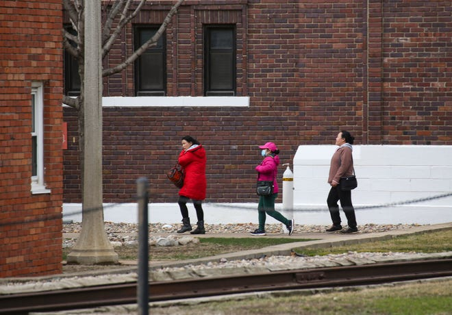 Employees walk to the main entrance to start their shift on Wednesday, March 24, 2021 at the Smithfield Foods in Sioux Falls.